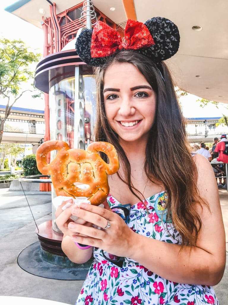 Megan enjoying a Mickey shaped pretzel in Tomorrowland @ Magic Kingdom Park   A Mickey Pretzel is considered a snack under the Disney Dining Plan